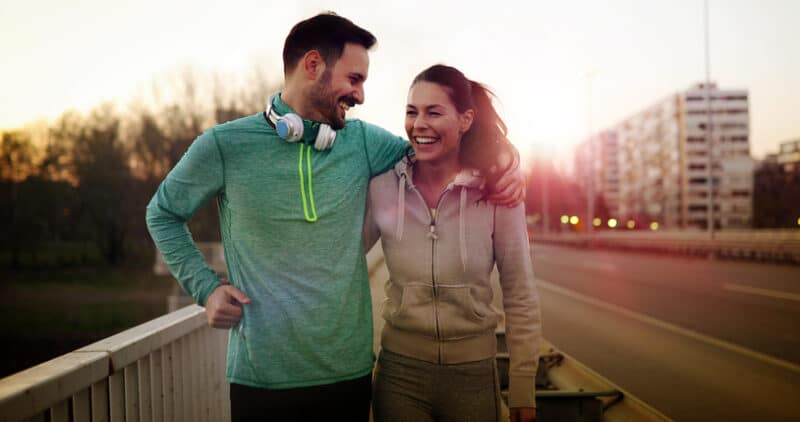 Young attractive couple running outside on sunny day